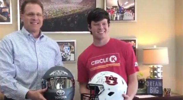 Gus Malzahn and Erik Jones swap helmets.