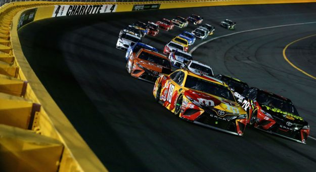 Cars race around Charlotte Motor Speedway in tight quarters.