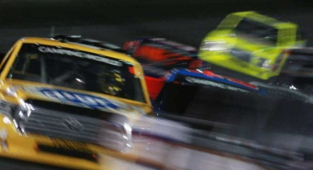 Camping World Truck Series vehicles circle the track at Charlotte Motor Speedway