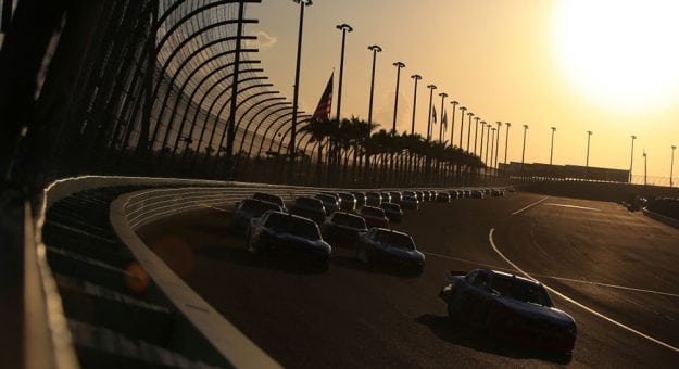 Cars on track at Homestead-Miami Speedway at sunset with palm trees behind the catchfence