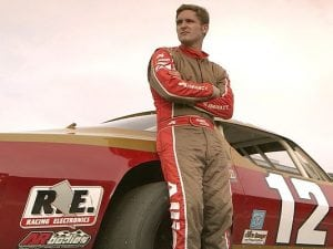 Robbie Allison stands by his red and gold race car