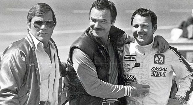 Hal Needham, Burt Reynolds and Stan Barrett at a race track in the early 1980s.