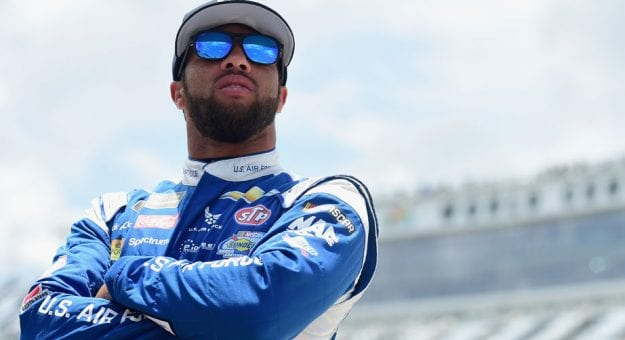 Bubba Wallace stands with arms crossed at the track.