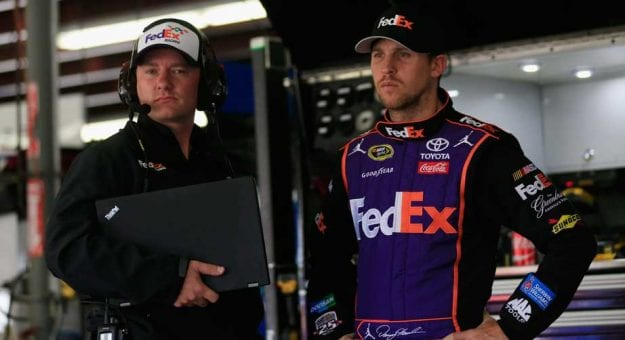 Mike Wheeler and Denny Hamlin stand in the garage.