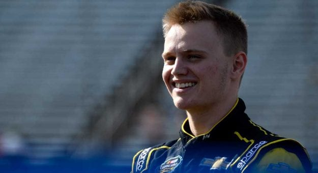 Justin Haley smiles while standing in the garage area.