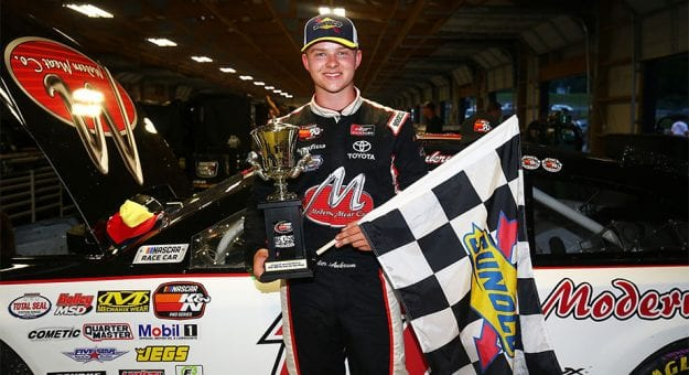 Tyler Ankrum poses with the checkered flag