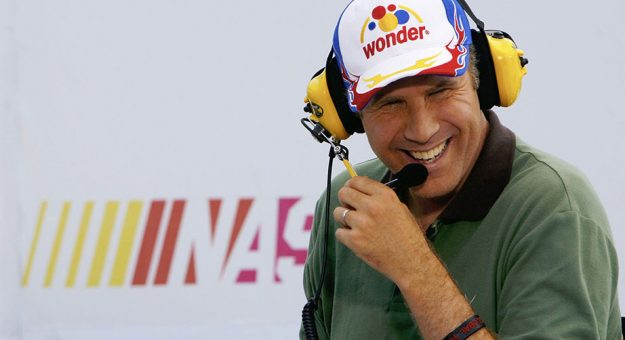 Will Farrell laughs while wearing a headset at a NASCAR race.