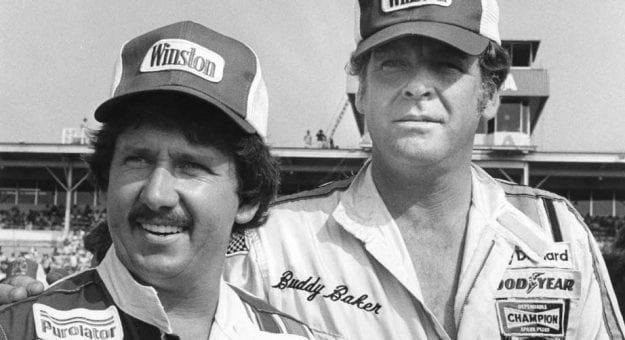 Neil Bonnett and Buddy Baker stand in the garage area at a race.