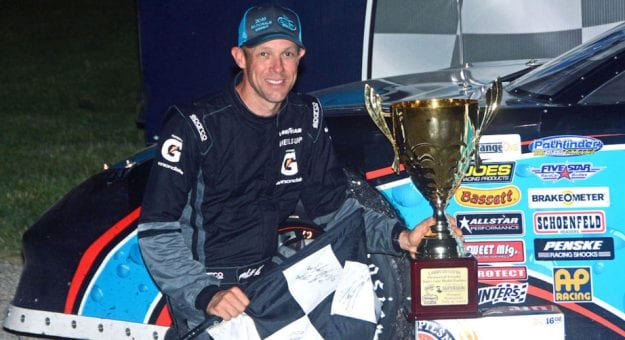 Matt Kenseth poses with the checkered flag after winning at Slinger