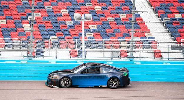 Joey Logano drives the Next Gen prototype, with smaller rear spoiler, near the outside retaining wall at ISM Raceway.