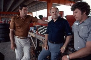 TALLADEGA, AL - 1980: Driver Buddy Baker (L), car owner Harry Ranier (C) and crew chief Waddell Wilson (R) discuss strategy in the garage area at Alabama International Motor Speedway prior to a NASCAR Cup race. (Photo by ISC Images & Archives via Getty Images)