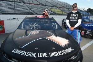"MARTINSVILLE, VIRGINIA - JUNE 10: Bubba Wallace, driver of the #43 Richard Petty Motorsports Chevrolet, wears a ""I Can't Breath - Black Lives Matter"" t-shirt under his firesuit in solidarity with protesters around the world taking to the streets after the death of George Floyd on May 25, stands next to his car painted with ""Compassion, Love, Understanding"" prior to the NASCAR Cup Series Blue-Emu Maximum Pain Relief 500 at Martinsville Speedway on June 10, 2020 in Martinsville, Virginia. (Photo by Jared C. Tilton/Getty Images) 