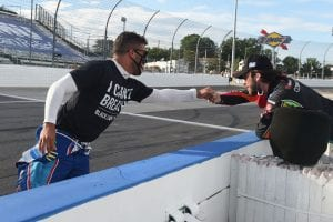 "MARTINSVILLE, VIRGINIA - JUNE 10: Bubba Wallace, driver of the #43 Richard Petty Motorsports Chevrolet, wears a ""I Can't Breathe - Black Lives Matter"" t-shirt under his firesuit in solidarity with protesters around the world taking to the streets after the death of George Floyd on May 25, and Daniel Suarez, driver of the #96 CommScope Toyota, bump fist on the grid prior to the NASCAR Cup Series Blue-Emu Maximum Pain Relief 500 at Martinsville Speedway on June 10, 2020 in Martinsville, Virginia. (Photo by Jared C. Tilton/Getty Images) 